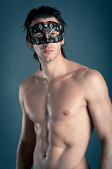 Portrait of young man shirtless with mask