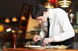 working waiter in uniform at restaurant
