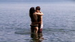 Beautiful couple play in the water slow motion