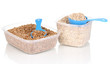 Measuring spoons and plastic containers with grain isolated
