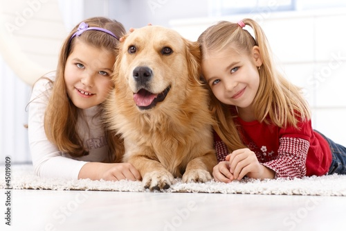 Happy girls with dog smiling at home