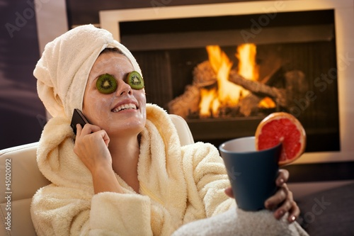 Happy woman in facial pack on phone