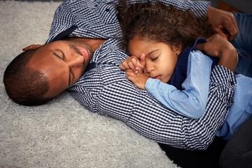 Ethnic father and little girl sleeping on floor