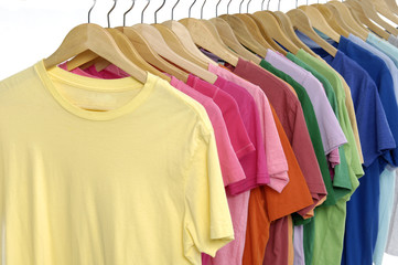 Rainbow colors. Choice of casual clothes on wooden hangers