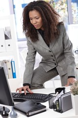 Ethnic businesswoman typing on keyboard