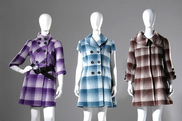 Set of Three dummies dressed in coat on gray background