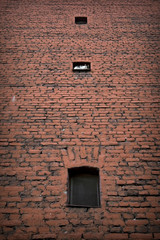 Brick wall with small dark windows and cat