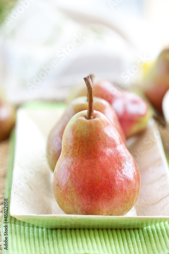 Red ripe pears in a mother-of-pearl bowl