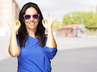 middle aged woman doing approval gesture at road
