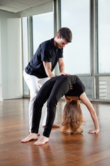 Instructor Adjusting Woman's Yoga Posture
