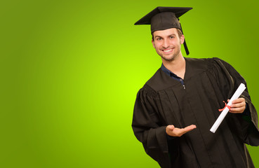 Young Man In Graduation Gown Holding Certificate