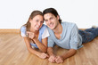 Cheerful couple laying down wooden floor