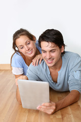 Couple using tablet laying on the floor at home
