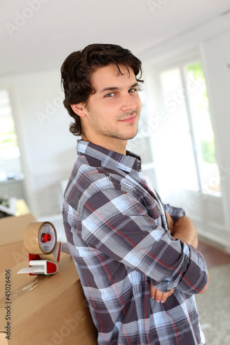 Young man packing boxes to move in new flat