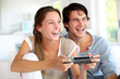 Young couple playing video games at home