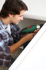 Repairman fixing door with electric drill