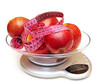 red apples with measure tape on electronic scale, diet concept