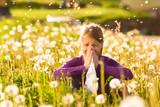 Mädchen auf Wiese mit Pusteblumen und Allergie