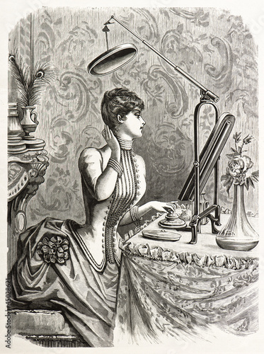elegant woman looking at mirror. engraved illustration 1885