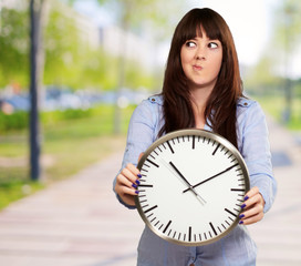 A Young Girl Holding A Clock And Making Face