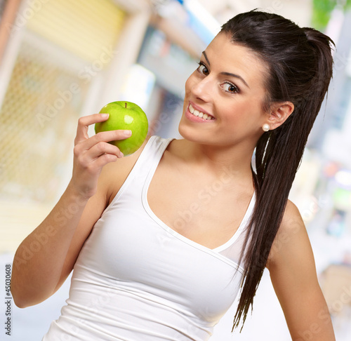 Young woman holding and eating an apple