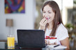 Cute woman eating breakfast while working at home
