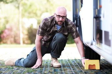 Mann schiebt Keil unter den Wohnwagenreifen