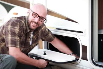 Mann packt seinen Wohnwagen voll