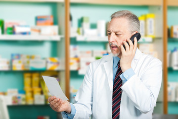 Pharmacist talking at the phone in his store