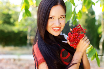 beautiful girl in the autumn park with the viburnum berry