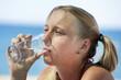 Девушка на пляже пьет чистую воду