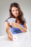 Woman playing cards with ace of hearts in her hand