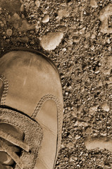 Hiking boot off-road shoe hard arid dried soil sepia vertical