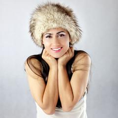 Uśmiechnięta piękna kobieta w czapce chroniącej przed zimą