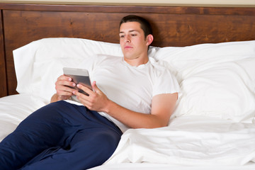 Young man reading tablet computer in bed