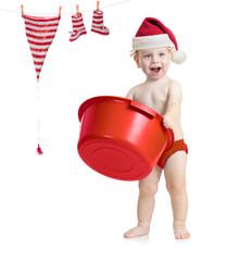 Happy kid in Santa's hat washing his accessories