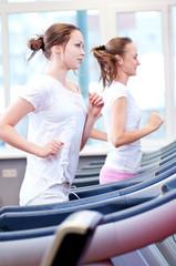 Two young sporty women run on machine