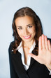 Businesswoman with stop gesture, over blue