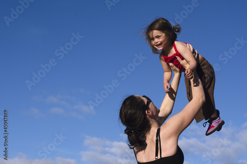 Mother holds her daughter up in the air