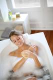 Beautiful woman using bath sponge