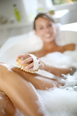 Woman in bathtub scrubbing her legs