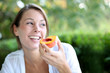 Smiling woman eating peach for breakfast