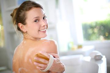 Gorgeous woman scrubbing her back in bath