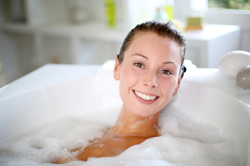 Smiling woman enjoying taking a bath