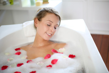 Beautiful woman relaxing in bath with rose petals