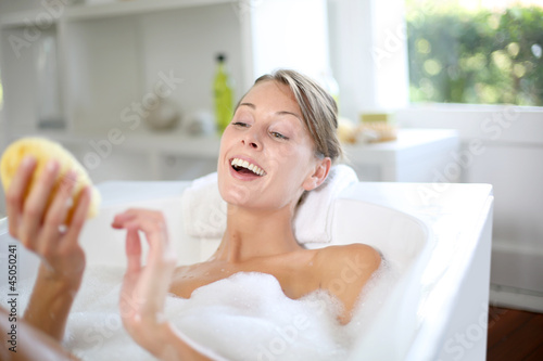 Beautiful woman using bath sponge