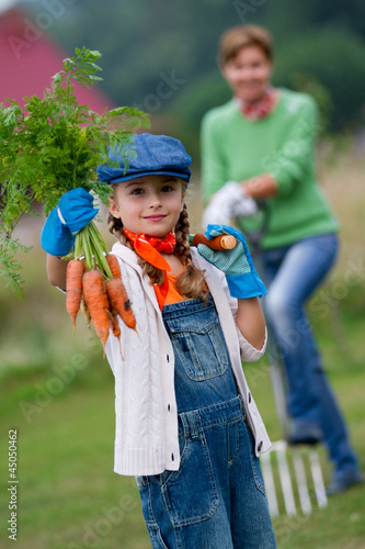 Autumn gardening - lovely girl with bunch of carrots