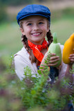 Autumn gardening - lovely girl with picked zucchini vegetables