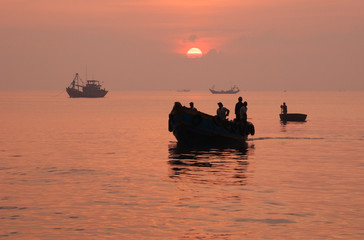 Silhouette of fishing boat return to port after a night of fishi