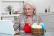 Older woman knitting at a laptop